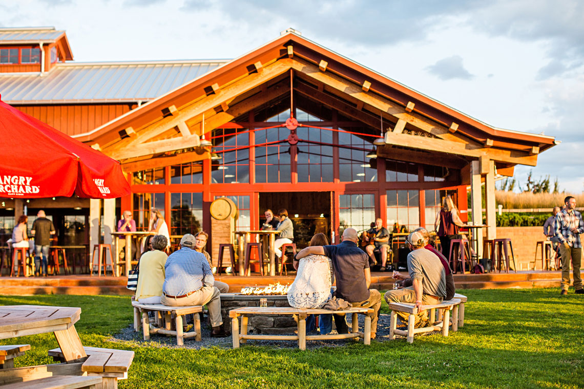 Close up of Angry Orchard building with people, green lawn and blue sky